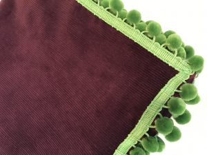 "Aubergine corduroy with green pom poms (42""/1.07m sq) £60"